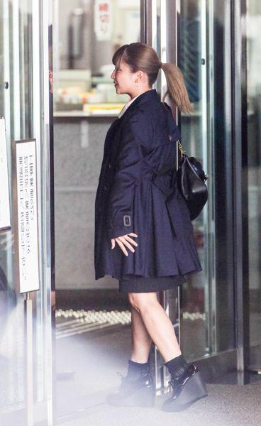 茶髪を束ね、紺のコートで/(C)日刊ゲンダイ
