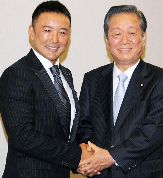 就任会見で握手する共同代表の山本、小沢両氏/(C)日刊ゲンダイ