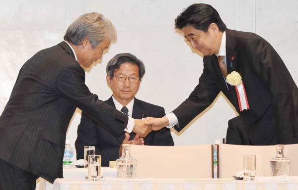 榊原・経団連会長(左)と握手する安倍首相(C)日刊ゲンダイ