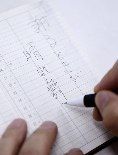 手帳にメモを(C)日刊ゲンダイ