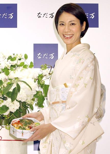 高級食材の乗ったお重を手に笑顔(C)日刊ゲンダイ