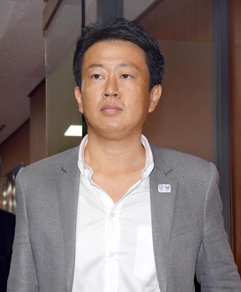 シャツがはだけすぎの野田特別秘書(C)日刊ゲンダイ