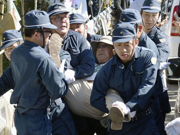 ヘリパッド建設に反対し座り込みをしていた男性を排除する機動隊員ら(C)共同通信社