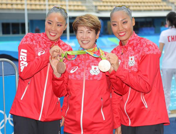 井村コーチ(央)の誕生日をメダルで祝った乾・三井ペア(C)JMPA