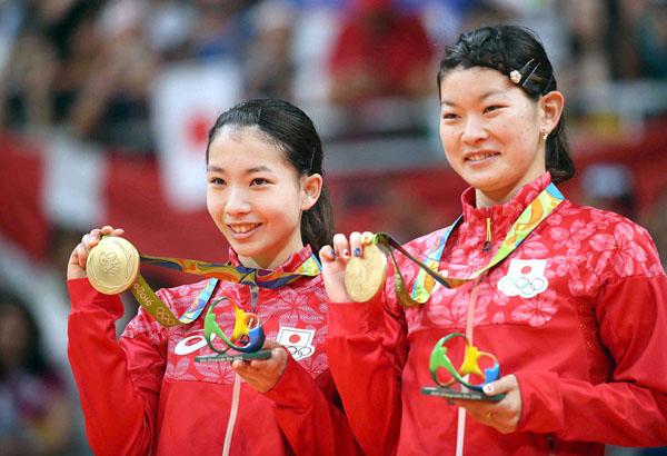 笑顔で金メダルを手にする高橋(右)と松友(C)真野慎也/JMPA