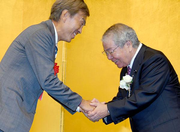 パーティーで石原経済再生相と握手をする内田茂都議(C)日刊ゲンダイ