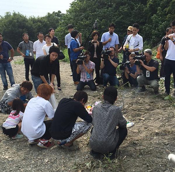 現場に花を供える人たち(C)日刊ゲンダイ
