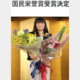 伊調馨は花束を手に表情を崩した(C)日刊ゲンダイ