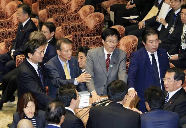 強行採決に講義する野党議員を静観する安倍首相(C)日刊ゲンダイ
