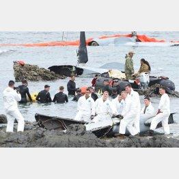 墜落したオスプレイ残骸のそばで笑顔で記念撮影する米兵(琉球新聞提供)
