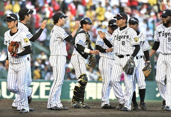 逆転勝利でタッチを交わす阪神ナイン(C)共同通信社