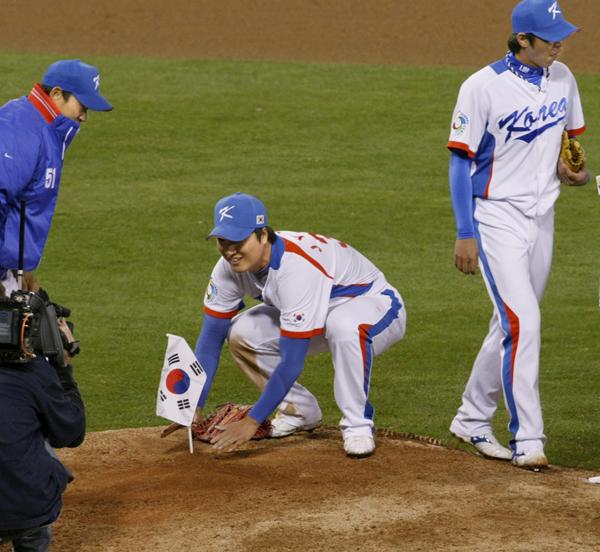 日本を破り、マウンドに国旗を立てる韓国の選手(C)共同通信社