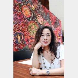 大作「薔薇の神曲」を背景に(C)日刊ゲンダイ