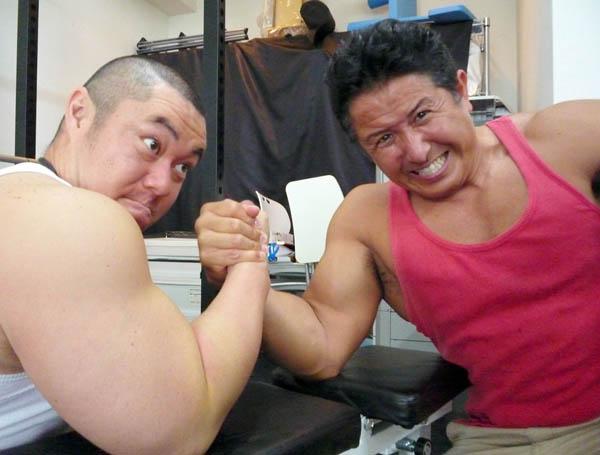 ジム開設を祝福しに来た芸人・ジャスティス岩倉(左)と腕相撲する坂本一生/(C)日刊ゲンダイ