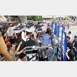 安倍首相の演説中に反自民の横断幕やプラカードを掲げる一団と競り合う党関係者(C)日刊ゲンダイ