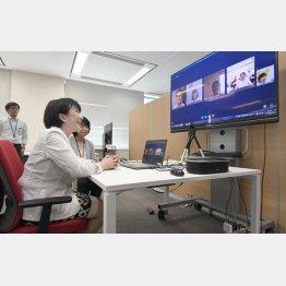 テレワーク中の総務省職員らとインターネットを通じて話す高市総務相(C)共同通信社