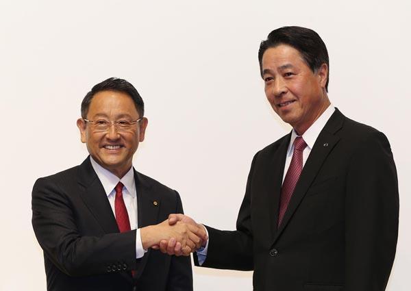ガッチリと握手した豊田社長(左)と小飼社長/(C)日刊ゲンダイ