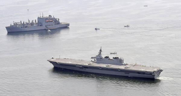 初の米艦防護(海上自衛隊の護衛艦「いずも」=手前、左上は停泊中の米海軍補給艦)/(C)共同通信社
