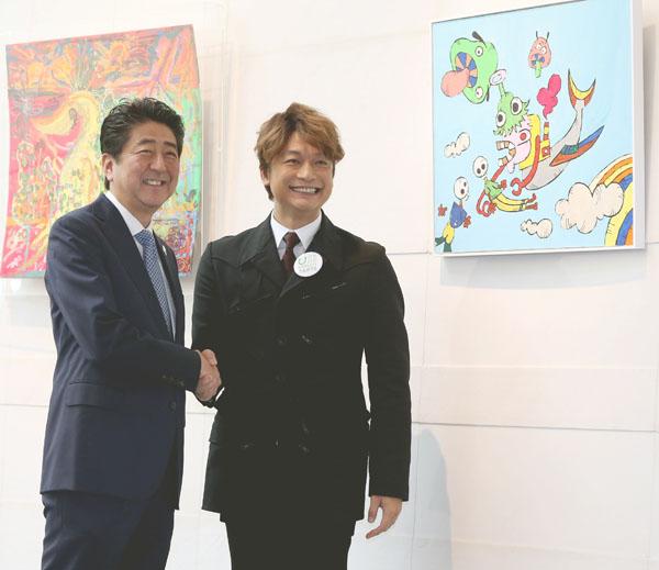 安倍首相と握手する香取慎吾(C)日刊ゲンダイ