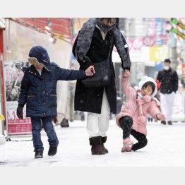 転びそうになりながら歩く親子連れ(2016年西日本大雪・福岡市)(C)共同通信社