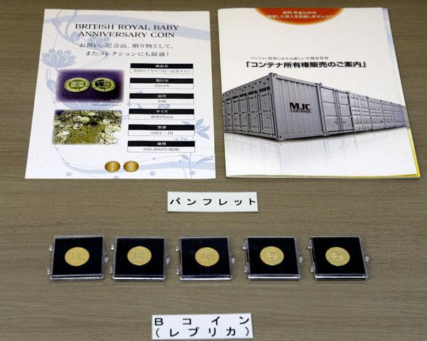 押収されたパンフレットとコインのレプリカ(C)共同通信社