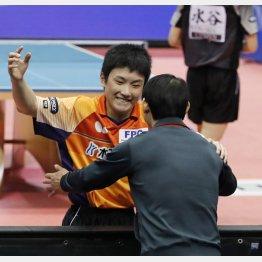 全日本選手権で水谷を下し、コーチを務める父の宇さんと抱き合う張本(C)日刊ゲンダイ