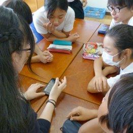 授業で使う分にはいいが…(スマートフォンを見ながら話し合う高校生と小学生)(C)共同通信社