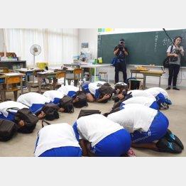 小学校で行われた避難訓練で身をかがめる児童(C)共同通信社