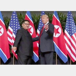 国旗の前で固い握手(C)ロイター