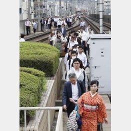 停止した電車から降りて線路を歩く人々(C)共同通信社