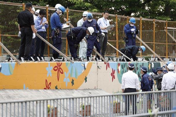 女児が下敷きになったブロック塀周辺を調べる捜査員ら(C)共同通信社