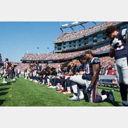 試合開始前、国歌斉唱時に片膝をつくニューイングランド・ペイトリオッツの選手ら(C)共同通信社