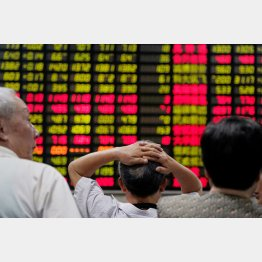 株価ボードを不安げに眺める投資家(C)ロイター