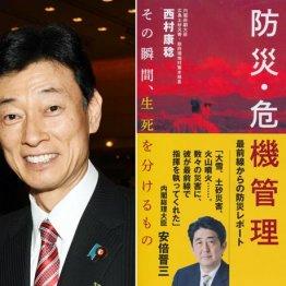 西村官房副長官(左)と4年前に出版した「命を守る防災・危機管理」
