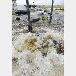道路脇のマンホールからあふれる水=2015年9月、栃木県小山市(C)共同通信社