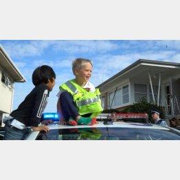 パトカーの上で笑顔のザッカリー君(オークランド市警のフェイスブックに投稿された動画より)