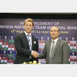 カンボジア協会会長と握手する本田圭佑(左)/(C)共同通信社