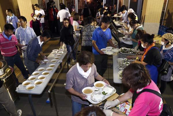 北海道厚真町の避難所で炊き出しに並ぶ人たち(C)共同通信社