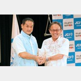 握手する玉城デニー氏(左)と佐喜真淳氏(C)日刊ゲンダイ
