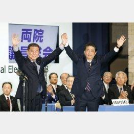 党総裁選を終え石破元幹事長(左)と手を取り合う(C)共同通信社