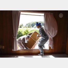 北海道厚真町で被災した住宅の窓から家財道具を運び出す人たち(C)共同通信社