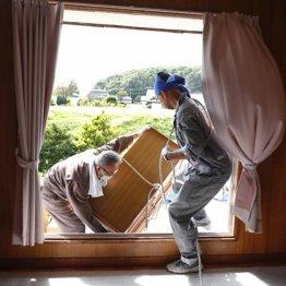 北海道厚真町で被災した住宅の窓から家財道具を運び出す人たち