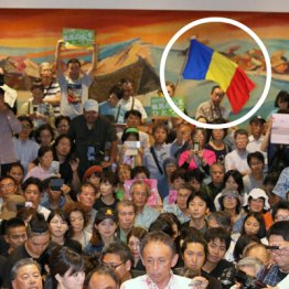 沖縄県知事選に圧勝し、報道陣に囲まれる玉城デニー氏(円内が三色旗)