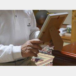 自殺した男性職員の写真を手に岡山県内の自宅で取材に応じた父親(C)共同通信社