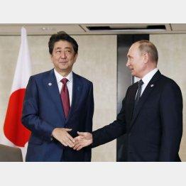 会談前にロシアのプーチン大統領(右)と握手する安倍首相(C)共同通信社