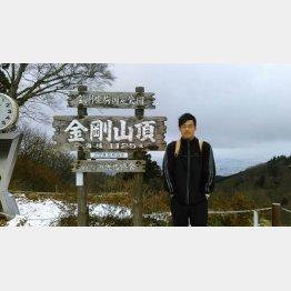 金剛山の頂きに立つファイナンシャルプランナーの藤原久敏さん(提供写真)