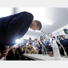 手前が問題のスプレー缶(謝罪する佐藤社長)/(C)共同通信社