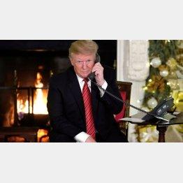 ホワイトハウスで「サンタクロース追跡作戦」の電話対応をするトランプ大統領(C)ロイター