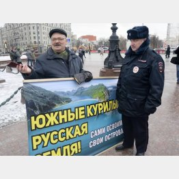 「南クリール諸島(北方領土)はロシアの土地だ」と書かれたプラカードを持つ男性(左)と警官(C)共同通信社
