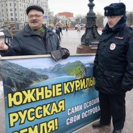 「南クリール諸島(北方領土)はロシアの土地だ」と書かれたプラカードを持つ男性(左)と警官